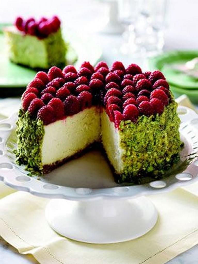 Cheesecake torta s pistacijevim drobljencem in malinami.